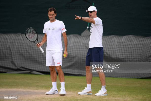 Roger Federer of Switzerland speaks to coach Ivan Ljubicic during a training session during Day Ten of The Championships - Wimbledon 2019 at All...