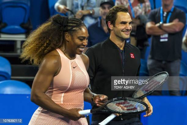 TOPSHOT Roger Federer of Switzerland stands alongside Serena Willams of the US following their mixed mixed doubles match in their sixth session on...
