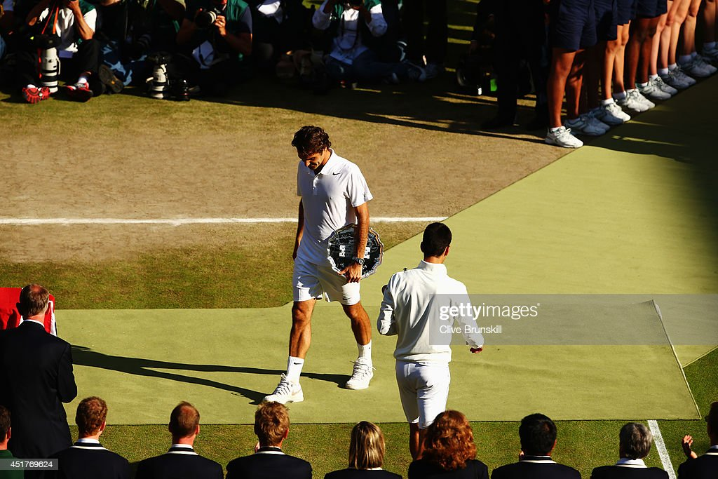 Roger Federer of Switzerland stands with the runner up trophy (l) as Novak Djokovic of Serbia walks the other way with the Gentlemen's Singles Trophy after the Gentlemen's Singles Final match on day thirteen of the Wimbledon Lawn Tennis Championships at the All England Lawn Tennis and Croquet Club on July 6, 2014 in London, England.