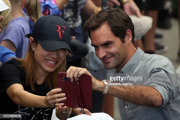 Roger Federer of Switzerland takes a selfie with a fan after a press conference ahead of US Open 2018 tournament in Louis Armstrong Stadium in...