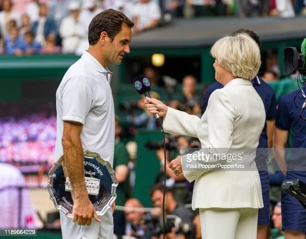 Roger Federer of Switzerland talks to BBC presenter Sue Barker after losing the gentlemen's singles final match against Novak Djokovic of Serbia on...