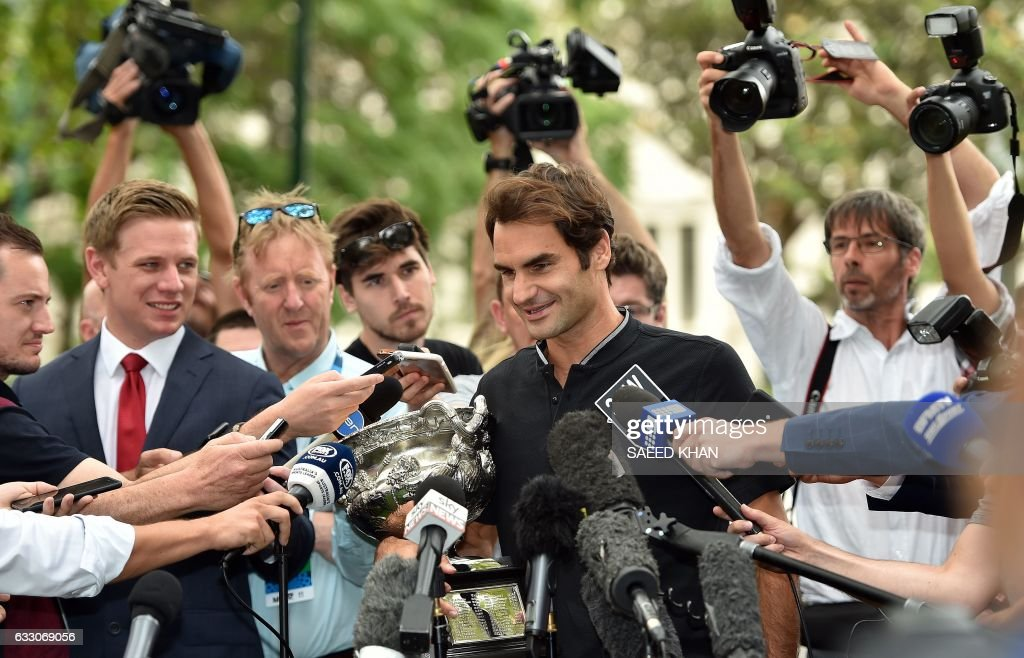 TOPSHOT - Roger Federer of Switzerland talks to media while holding the championship trophy the day after winning the Australian Open men's singles final for his 18th career Grand Slam in Melbourne on January 30, 2017. /