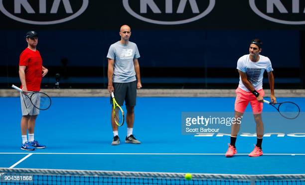Roger Federer of Switzerland talks with his coaches Severin Luthi and Ivan Ljubicic during a practice session ahead of the 2018 Australian Open at...