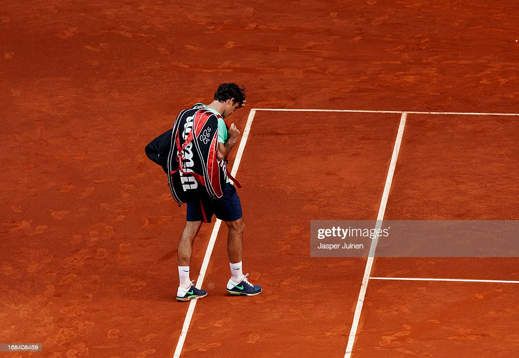 Roger Federer of Switzerland trudges off the pitch after his match against Kei Nishikori of Japan on day six of the Mutua Madrid Open tennis tournament at the Caja Magica on May 9, 2013 in Madrid, Spain.