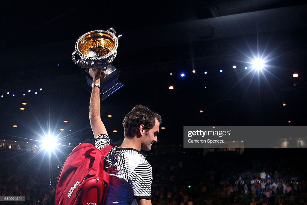 Roger Federer of Switzerland walks off court with the Norman Brookes Challenge Cup after winning the Men's Final match against Rafael Nadal of Spain on day 14 of the 2017 Australian Open at Melbourne Park on January 29, 2017 in Melbourne, Australia.