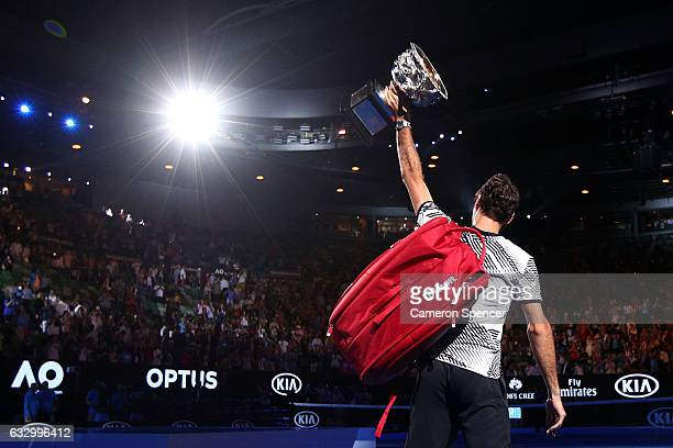 Roger Federer of Switzerland walks off court with the Norman Brookes Challenge Cup after winning the Men's Final match against Rafael Nadal of Spain...