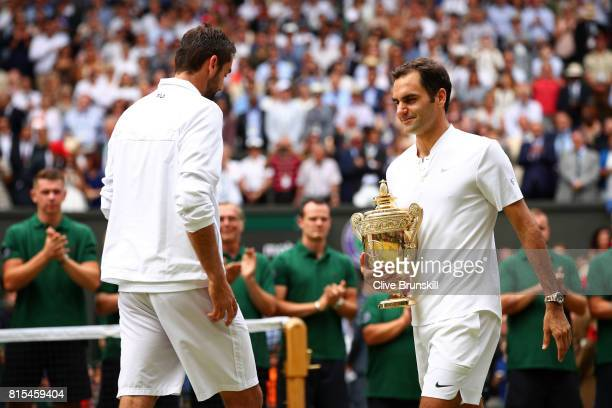 Roger Federer of Switzerland walks past runnerup Marin Cilic of Croatia after the Gentlemen's Singles final on day thirteen of the Wimbledon Lawn...
