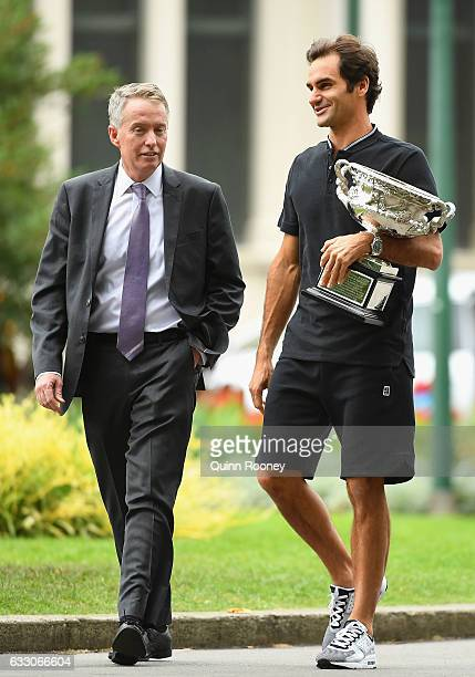 Roger Federer of Switzerland walks with Craig Tiley as he prepares to pose with the Norman Brookes Challenge Cup after winning the 2017 Australian...