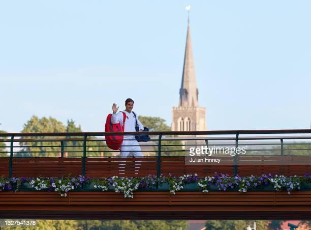 Roger Federer of Switzerland waves as he walks across the players bridge after losing his men's Singles Quarter Final match against Hubert Hurkacz of...