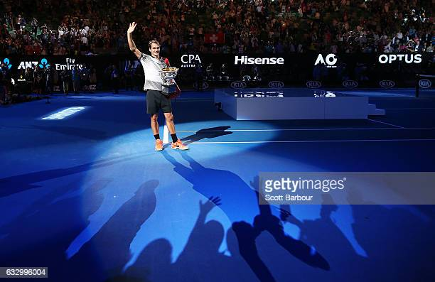 Roger Federer of Switzerland waves to fans in the crowd as he poses with the Norman Brookes Challenge Cup after winning the Men's Final match against...