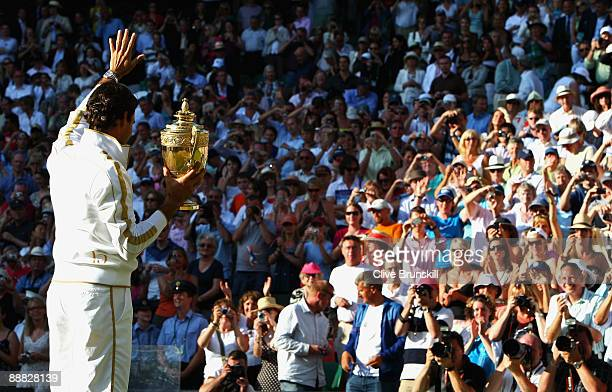 Roger Federer of Switzerland waves to the crowd as he celebrates with the trophy after the men's singles final match against Andy Roddick of USA on...