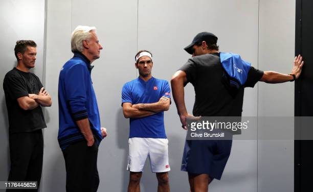 Roger Federer of Team Europe speaks with teammates Thomas Enqvist, Bjorn Borg and Rafael Nadal prior to his singles match against John Isner of Team...