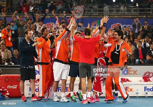 Roger Federer of the Indian Aces is congratulated by his team mates after breaking the serve of Novak Djokovic of the UAE Royals in his match during...