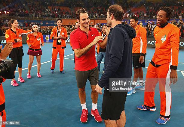 Roger Federer of the Indian Aces says goodbye to Pete Sampras and the rest of his team mates after his teams match against the UAE Royals during the...