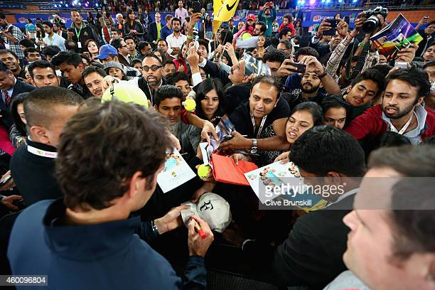 Roger Federer of the Indian Aces signs autographs after his victory in his match against Tomas Berdych of the Singapore Slammers during the Coca-Cola...