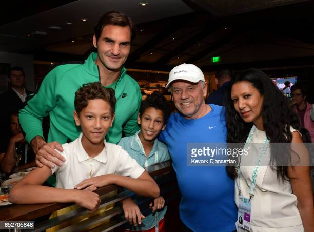 Roger Federer poses with celebrity chef Wolfgang Puck and his wife designer Gelila Assefa and their children Oliver Puck and Alexander Puck inside...
