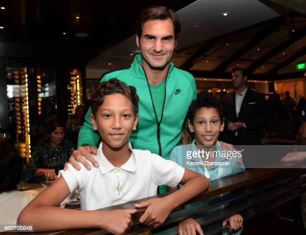 Roger Federer poses with the children of celebrity chef Wolfgang Puck Oliver Puck and Alexander Puck inside Spago at Desert Champions overlooking...