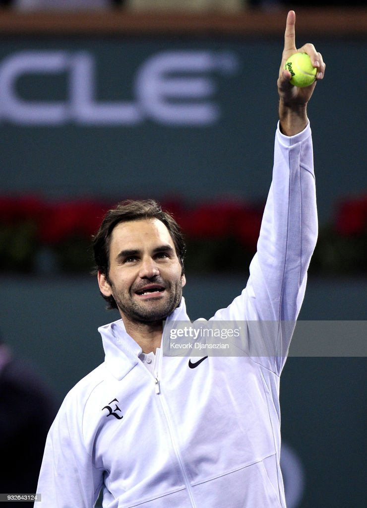 Roger Federer Switzerland looks to launch tennis balls to the crowd in the stands after defeating Hyeon Chung of Korea during Day 11 of BNP Paribas Open on March 15, 2018 in Indian Wells, California.