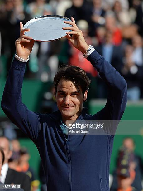 Roger Federerof Switzerland poses with the second place trophy after losing to Stanislas Wawrinka of Switzerland in their final match on day eight of...