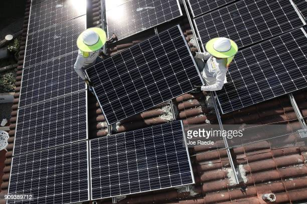 Roger Garbey and Andres Hernandez , from the Goldin Solar company, install a solar panel system on the roof of a home a day after the Trump...
