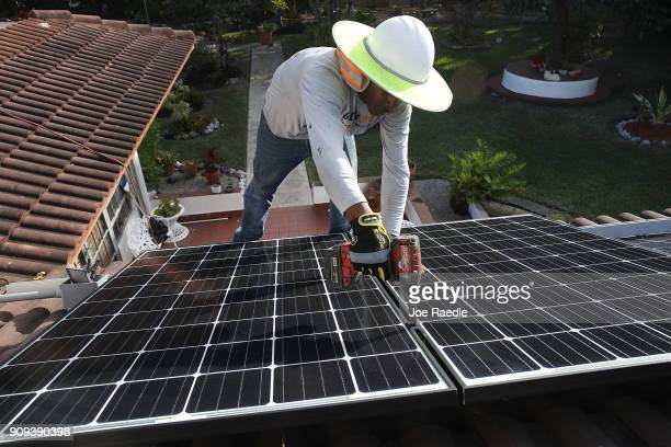 Roger Garbey, from the Goldin Solar company, installs a solar panel system on the roof of a home a day after the Trump administration announced it...