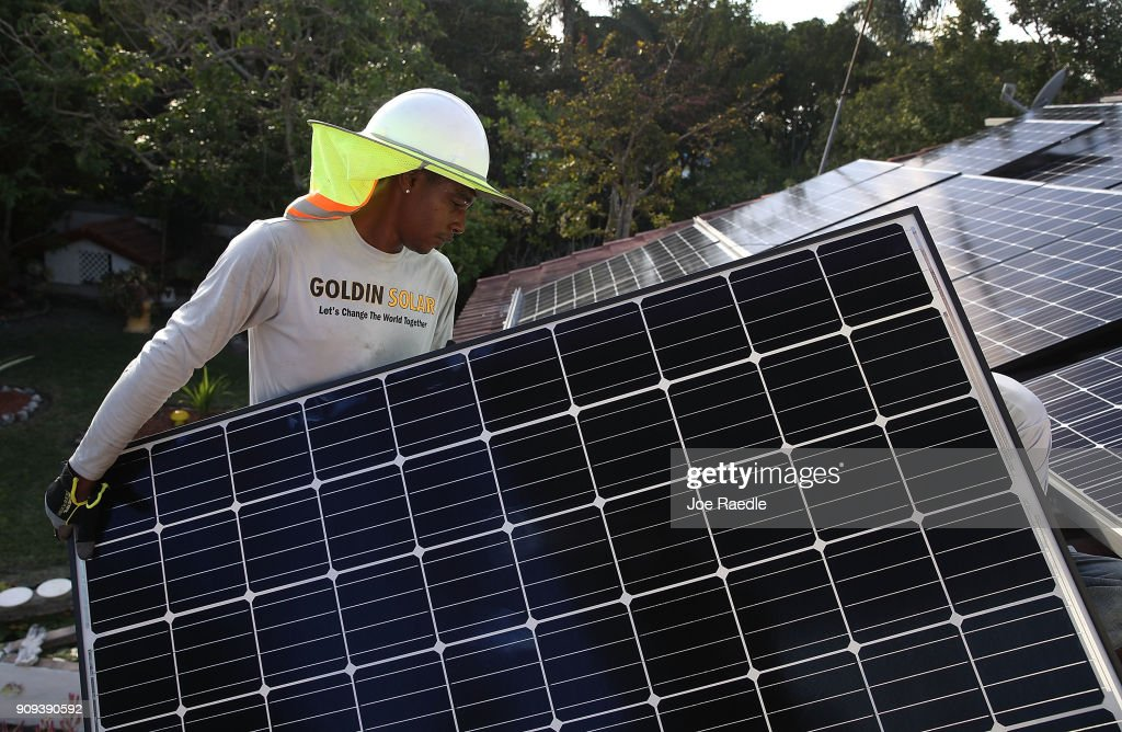 Roger Garbey, from the Goldin Solar company, installs a solar panel