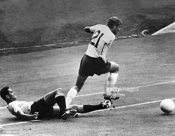 Roger Hunt England striker evades the tackle from Uruguay midfielder Pedro Rocha during the opening match of the 1966 FIFA World Cup at Wembley...