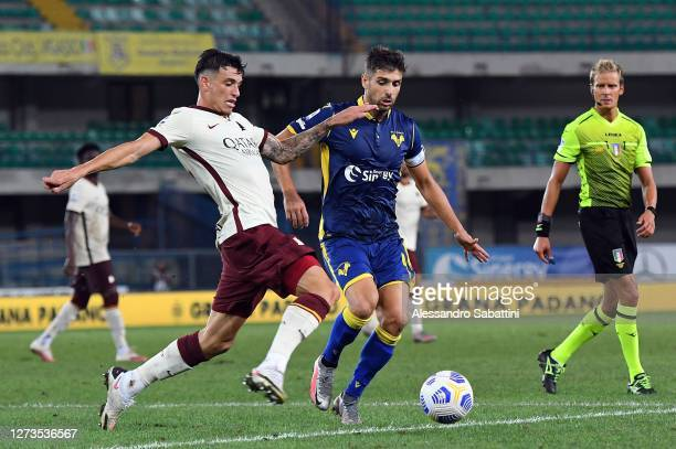 Roger Ibanez of As Roma competes for the ball with Miguel Veloso of Hellas Verona during the Serie A match between Hellas Verona FC and AS Roma at...