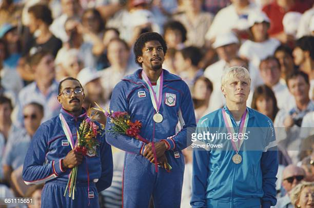 Roger Kingdom of the United States stands on the podium with his gold medal alongside silver medallist Greg Foster and bronze medallist Arto Bryggare...