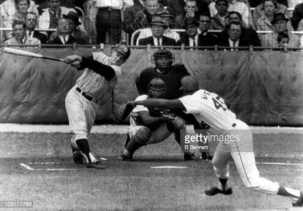 Roger Maris of the New York Yankees strikes out against Bob Gibson of the St Louis Cardinals as catcher Tim McCarver and umpire Bill McKinley look on...