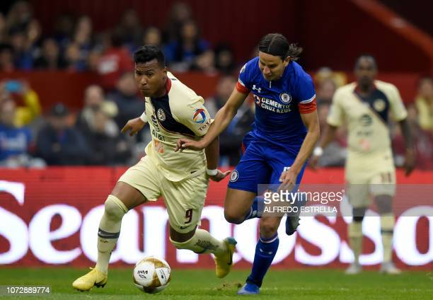 Roger Martinez of America vies for the ball with Igor Lichnovsky of Cruz Azul during the first round match of the final of the Mexican Apertura...