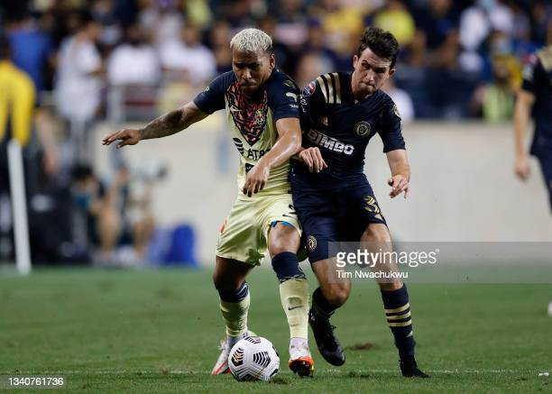 Roger Martínez of Club America and Leon Flach of Philadelphia Union challenge for possession during the semifinal second leg match of the CONCACAF...