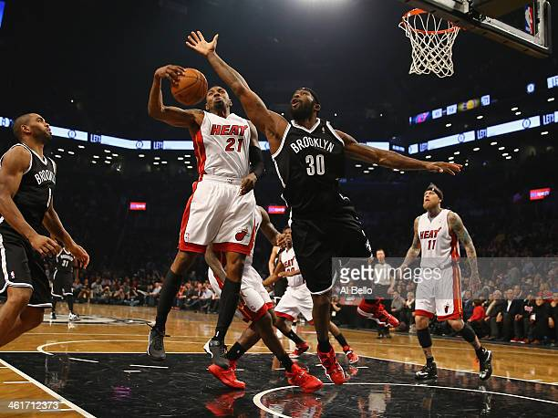 Roger Mason Jr #21 of the Miami Heat and Reggie Evans of the Brooklyn Nets reach for the ball during their game at the Barclays Center on January 10...