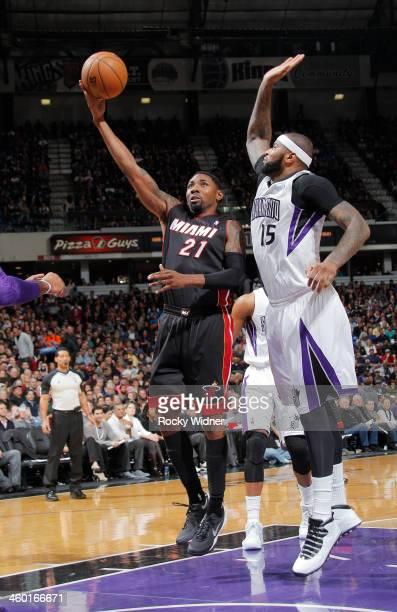 Roger Mason Jr #21 of the Miami Heat shoots against DeMarcus Cousins of the Sacramento Kings on December 27 2013 at Sleep Train Arena in Sacramento...