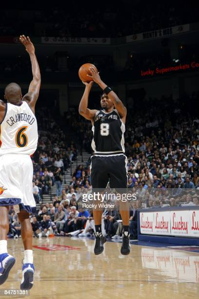 Roger Mason of the San Antonio Spurs shoots a jump shot over Jamal Crawford of the Golden State Warriors during the game at Oracle Arena on February...