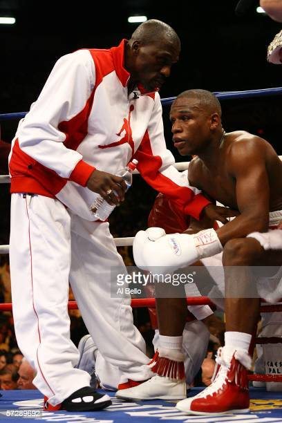 Roger Mayweather the trainer and uncle of Floyd Mayweather talks to his nephew during a round break against Zab Judah during the Welterweight...