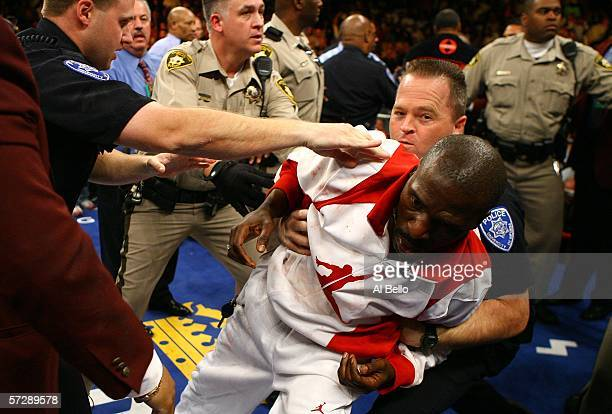 Roger Mayweather the uncle and trainer of Floyd Mayweather jumps into the ring and is held down by a cop after Floyd was hit below the belt by Zab...
