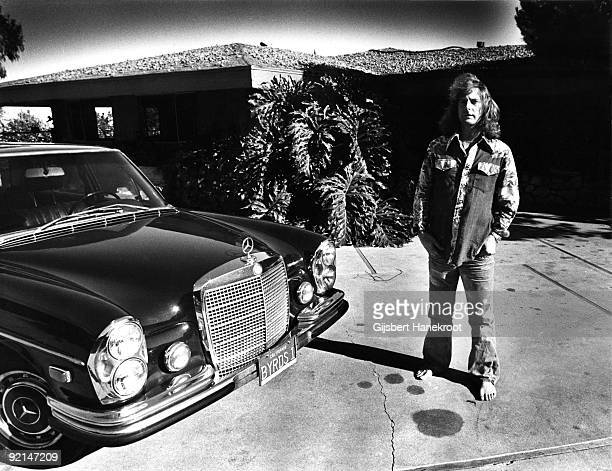 Roger McGuinn from the Byrds posed at home with a Mercedes car in Malibu California in 1974