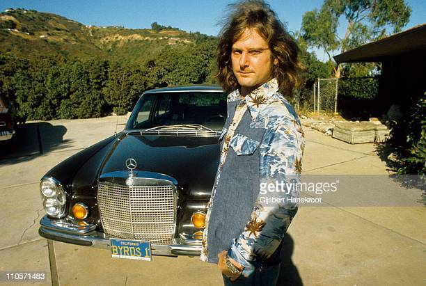 Roger McGuinn of The Byrds poses for a portrait in front of his Mercedes with a personalised numberplate in 1974 in Malibu California United States