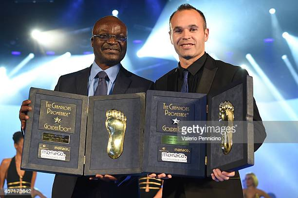 Roger Milla and Andres Iniesta receive the Golden Foot Award trophy during the Golden Foot Award 2014 ceremony at Sporting Club on October 13 2014 in...