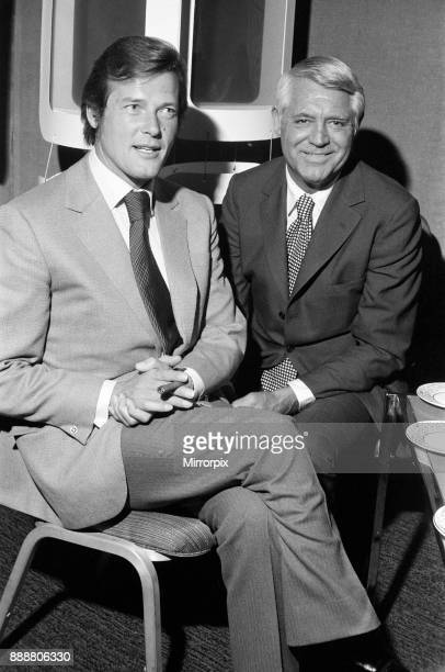 Roger Moore and Cary Grant sample one of their perfumes during their visit to their perfume company's trade show at The Inn in the Park Park Lane...