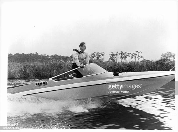 Roger Moore at the wheel of a speed boat in a scene from the film 'Live And Let Die' 1973
