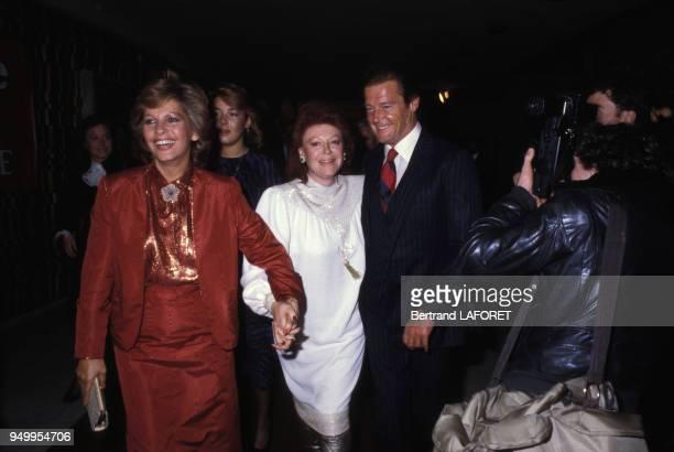 Roger Moore, avec à gauche son épouse Luisa Mattioli, et Régine et lors d'une soirée, circa 1980 à Paris, France.