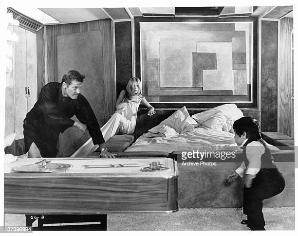Roger Moore chasing Hervé Villechaize while Britt Ekland huddles against the wall with a sheet wrapped around her in a scene from the film 'The Man...