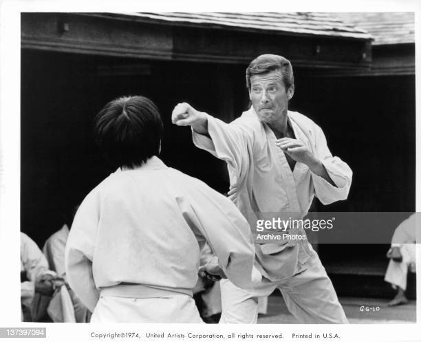Roger Moore engages in a martial arts match with an unknown actor in a scene from the film 'The Man With The Golden Gun' 1974