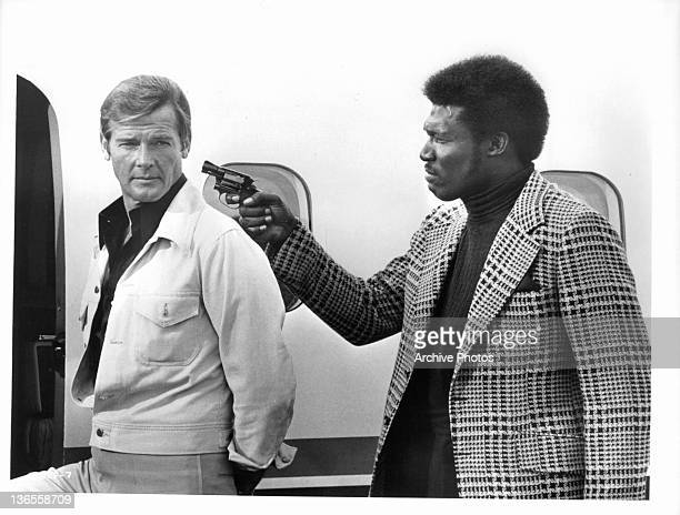 Roger Moore escorted unto a plane by gunpoint from an unknown actor in a scene from the film 'Live And Let Die' 1973