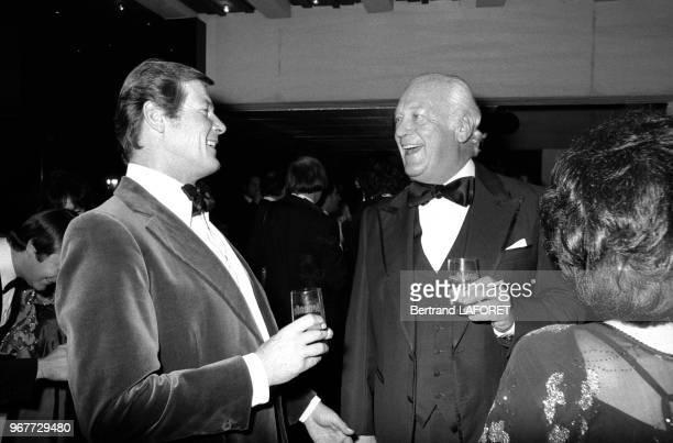Roger Moore et Curd Jurgens lors d'une soirée offerte par Van Cleef et Arpels à Gstaad en Suisse le 29 décembre 1977