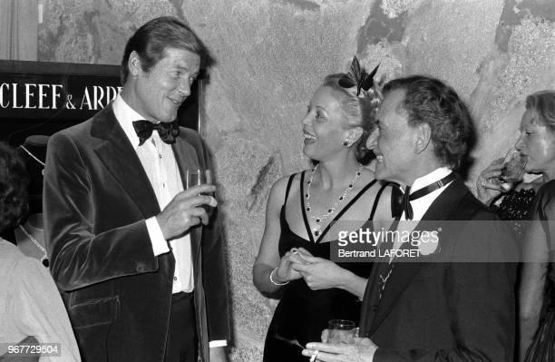 Roger Moore et le coiffeur Alexandre lors d'une soirée offerte par Van Cleef et Arpels à Gstaad en Suisse le 29 décembre 1977