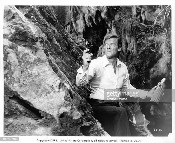 Roger Moore leaning against the side of a cliff with a thermos in one hand and a gun in the other hand in a scene from the film 'The Man With The...