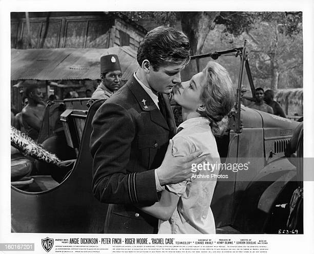 Roger Moore leaning in to kiss Angie Dickinson in a scene from the film 'The Sins Of Rachel Cade' 1961